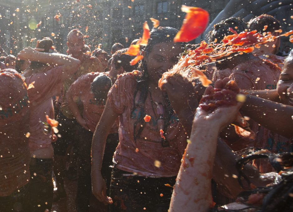 Participants hurl tomatoes in front of the Royal Palace, rear, turning Amsterdam's central Dam square into a red pulpy mess Sunday, Sept. 14, 2014.