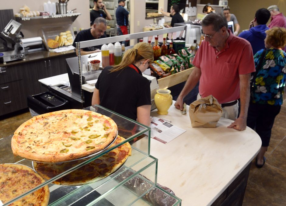 Bob Reedy of Guilderland, right, waits to pay for his order at Ruggiero's Pizza Deli & Catering on Carman Road in Guilderland on Oct. 17.