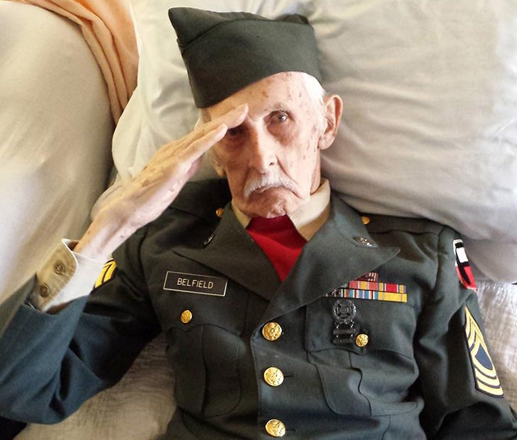Justus Belfield salutes in his army uniform from his bed at Baptist Health Nursing and Rehabilitation Center in Scotia on Nov. 11.