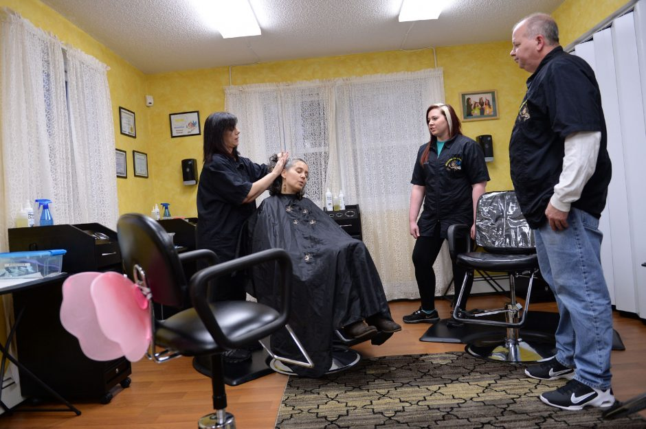 Gazette reporter Kelly de la Rocha gets her hair inspected for lice by Helaina Slader of Miracles on Lice, as Slader's husband, Bill, and daughter Mandee watch in Ballston Lake on Nov. 6.