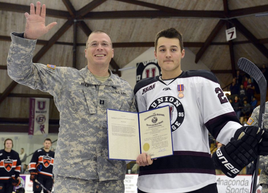 Capt. Timothy Neild of Guilderland, left, and Union College hockey player Kevin Shier are given a standing ovation at Messa Rink Saturday, November 15, 2014.