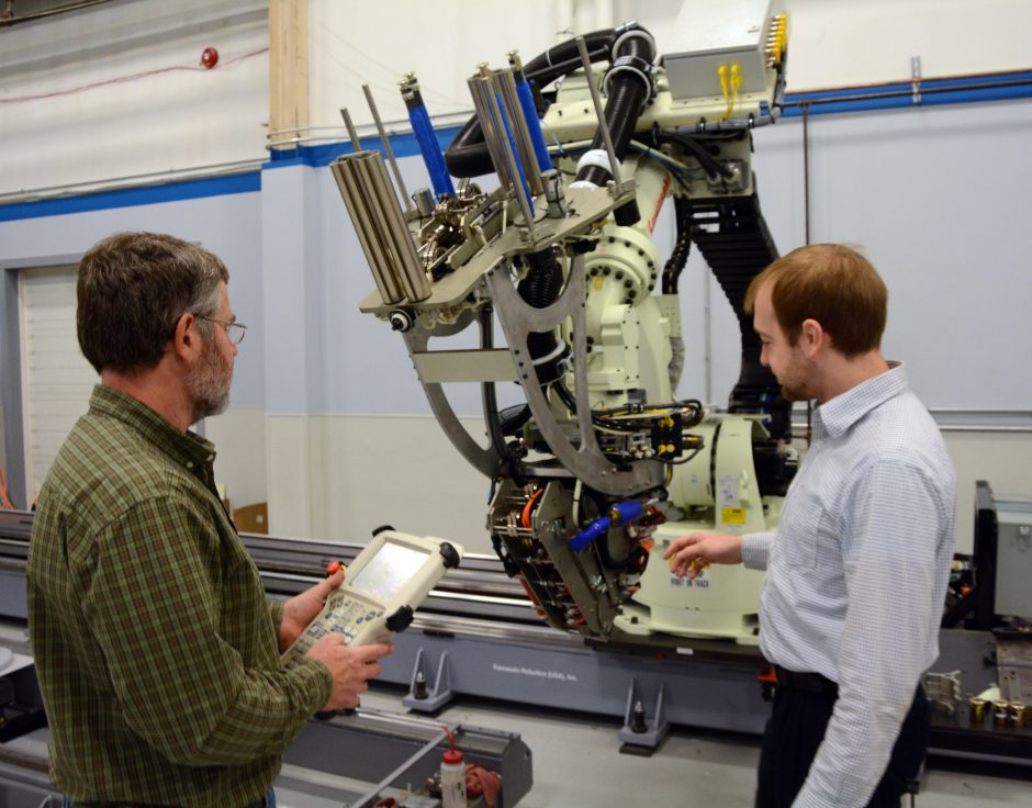 Mike Pasanen, left, chief engineer at Schenectady's Automated Dynamics, and Zack August, project engineer, demonstrate how an automated fiber-placement work cell used for making composite structures is used at the facility.