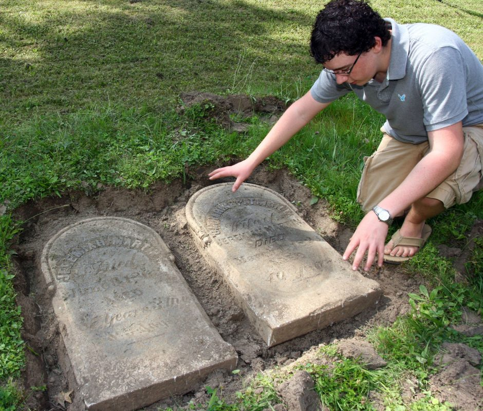 Ryan Weitz examines a pair of headstones dated 1863 and 1826 that he discovered when he saw a part of one showing in the Fultonville Cemetery on Friday.
