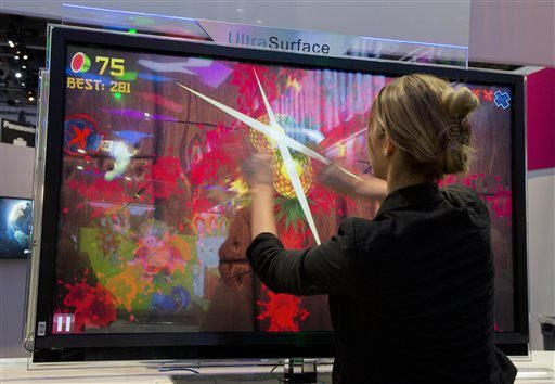 In this Jan. 10, 2013 photo, an attendee plays Fruit Ninja at the Panasonic booth at the Consumer Electronics Show in Las Vegas.