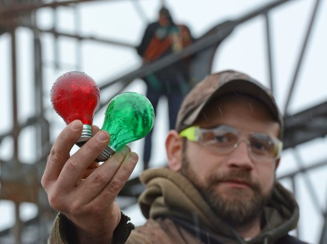 Ryan Mugits holds light bulbs.