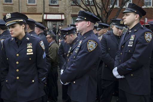 Some police officers turn their backs as Mayor Bill de Blasio speaks during the funeral of New York Police Department Officer Wenjian Liu, Sunday, Jan. 4, 2015, in the Brooklyn borough of New York.