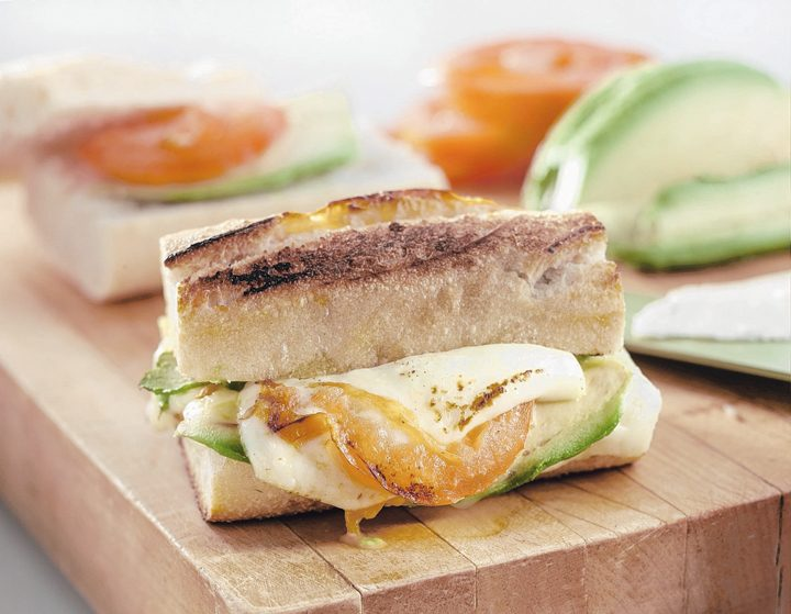 A crusty cheese breakfast sandwich can be adorned with avocado and tomato. (Chicago Tribune)