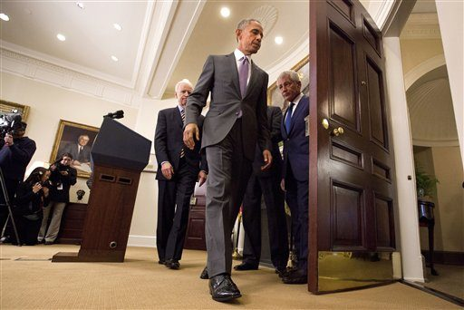 President Barack Obama leaves the Roosevelt Room of the White House in Washington, Wednesday, Feb. 11, 2015, followed by Vice President Joe Biden, left, Secretary of State John Kerry, obscured, and Defense Secretary Chuck Hagel, after speaking about th...