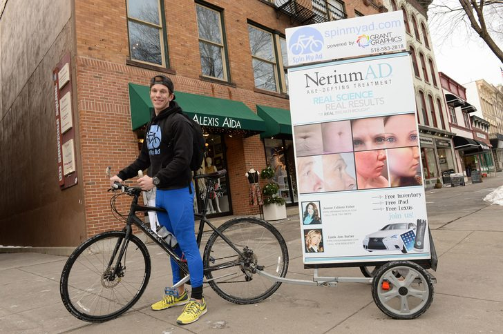 Kenny Goodwin Jr., founder and CEO of Spin My Ad, poses for a picture on his bicycle billboard in downtown Saratoga Springs on Thursday, January 29, 2015.