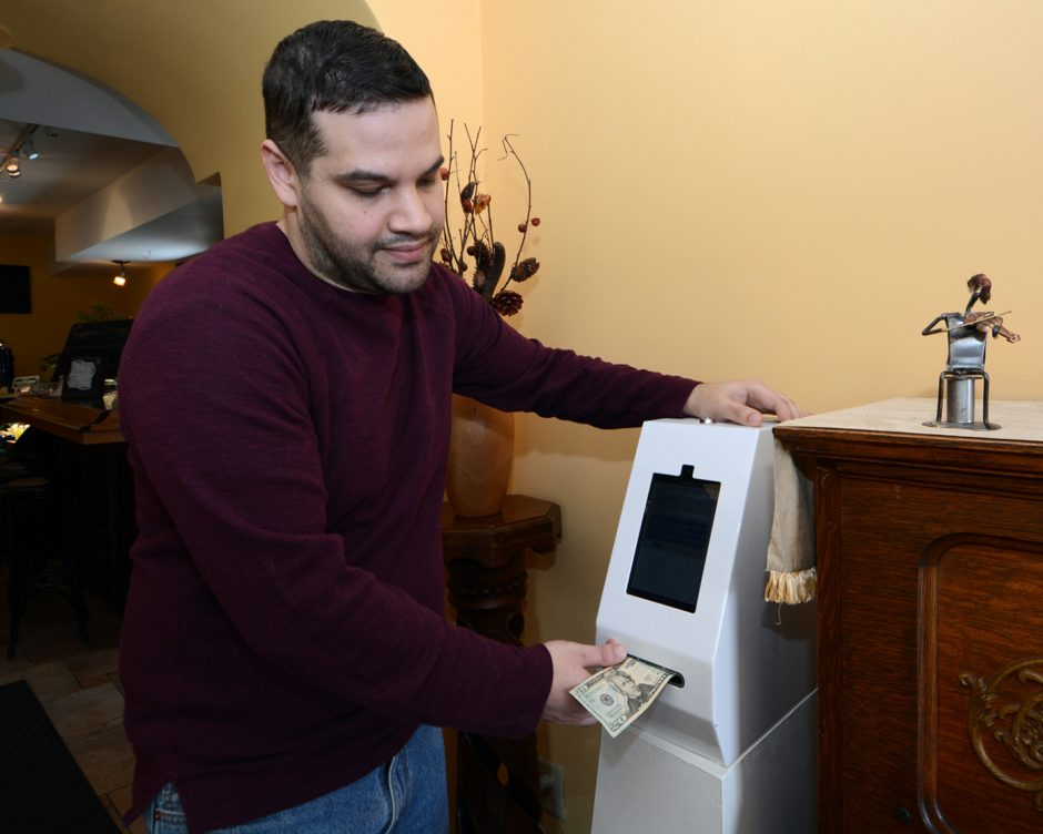 Paul Paterakis of NY Bitcoin Group, feeds a $20 bill into a Bitcoin ATM located in Tesoros Cafe' on Union St.