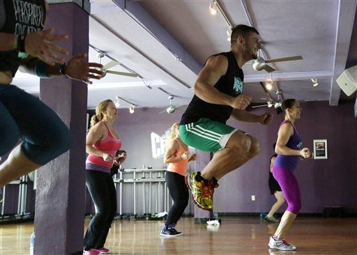 In this Monday, Feb. 2, 2015 photo, a participant jumps into the air as Carole Steinhauser, right, leads a Cutthroat Cardio class at a Crunch Gym in Miami Beach, Fla.