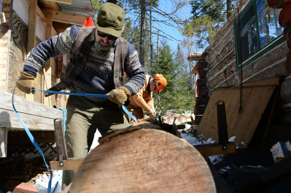 Structural preservationists Michael Frenette and John Wrolsen secure a log at environmentalist Anne LaBastille's cabin on an Adirondack lake on Wednesday. Frenette is going through the process of dismantling the structure and transporting it to the Adi...