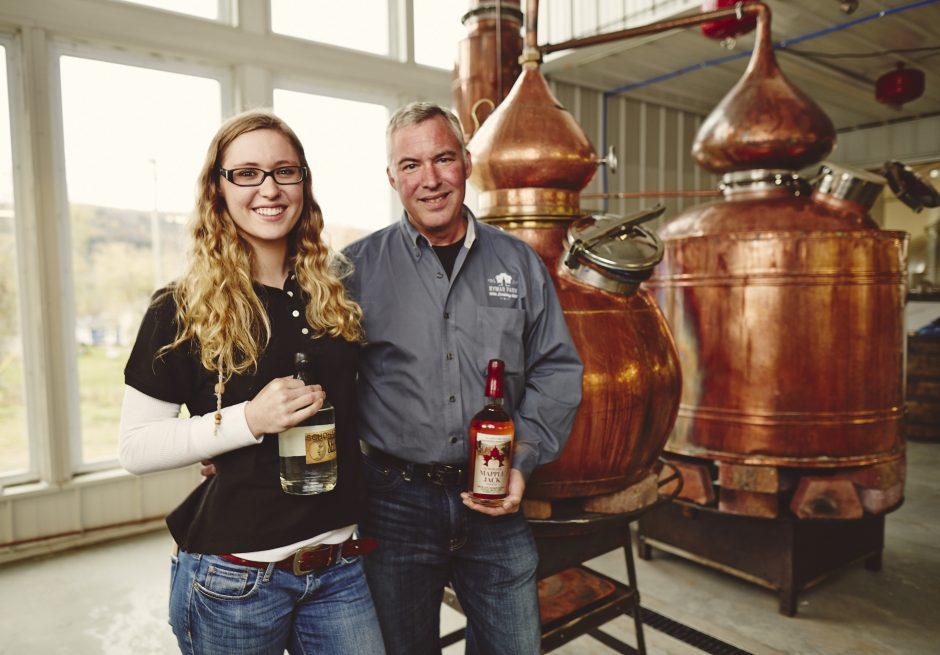 Ken Wortz, owner and head distiller at Kymar Farm Distillery, and daughter Marissa hold bottles of Schoharie Shine and Mapple Jack produced at the Schoharie County farm, winery and distillery. In the background are direct-fire pot stills. (photo provided)