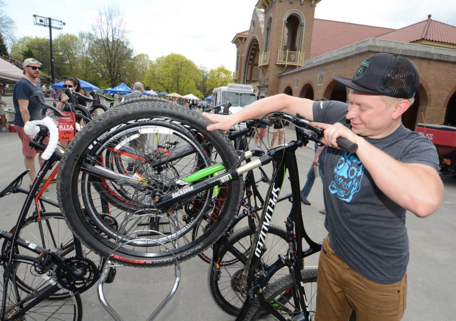 Matt Plaine of Plaine and Son pulls a Specialized mountain bike from the rack for a customer to try out during the fifth annual Bike Expo in Washington Park in Albany on Sunday, May 3, 2015.