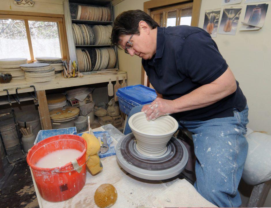 Ballston Lake Pottery owner James Sankowski uses a momentum kick wheel to make a bowl at his shop.