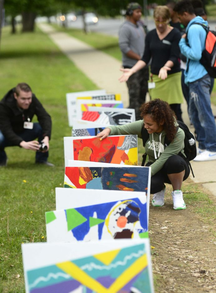 Schenectady High School student Maeliza Roulhac adjusts her painting on display in front of the school Tuesday.