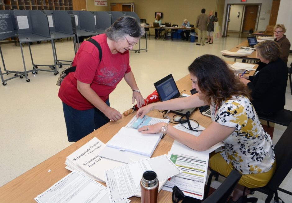 Deb Kreifels, left, signs in with Carrie Nyc-Chevrier while voting at Niskayuna High School during school board elections on Tuesday, May19,2015.