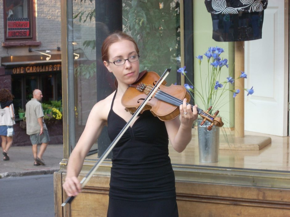 Fiddler Sara Raab busks in front of Lifestyles clothing store on Broadway in Saratoga Springs in this 2009 photo.