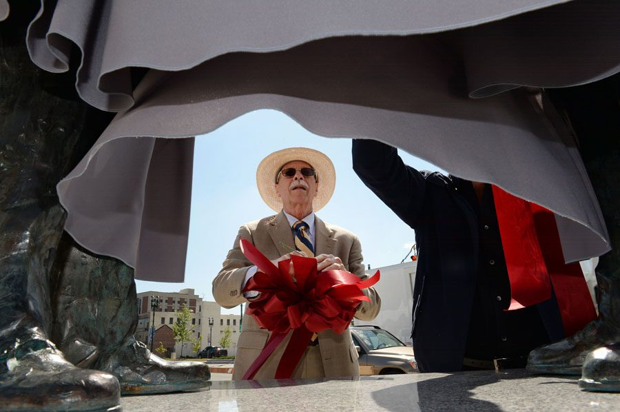 Robert Ray, of Schenectady, center, a former GE employee, attaches a ribbon to bronze statues of Thomas Edison and Charles Steinmetz before they were unveiled on Erie Boulevard in downtown Schenectady on Friday, May 22, 2015.