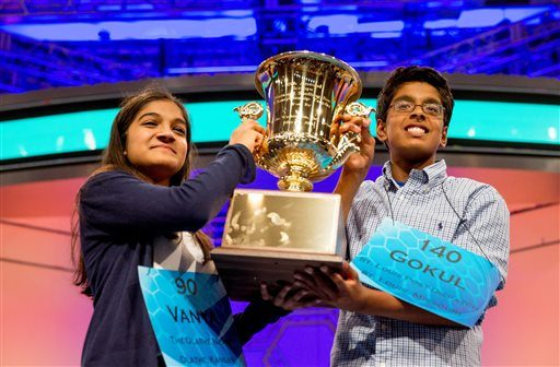 Vanya Shivashankar, left, 13, of Olathe, Kan., and Gokul Venkatachalam, 14, of St. Louis, hold up the championship trophy as co-champions after winning the finals of the Scripps National Spelling Bee, Thursday, May 28, 2015, in Oxon Hill, Md.