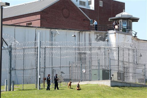 Law enforcement officers with bloodhounds stand guard at one of the entrances to the Clinton Correctional Facility in Dannemora on Saturday.