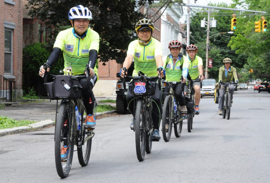 A team of bicyclists from Kunming, China, Schenectady's sister city, pedal in the Stockade on their way from Plymouth, Mass., to San Bernadino, Calif., on Monday.
