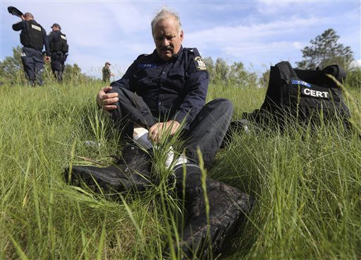 A law enforcement officer takes off his boots during a break in the search for two prisoners who escaped from the Clinton Correctional Facility on Saturday, June 13, 2015, in Saranac, N.Y. Authorities are in the eighth day of searching for David Sweat ...