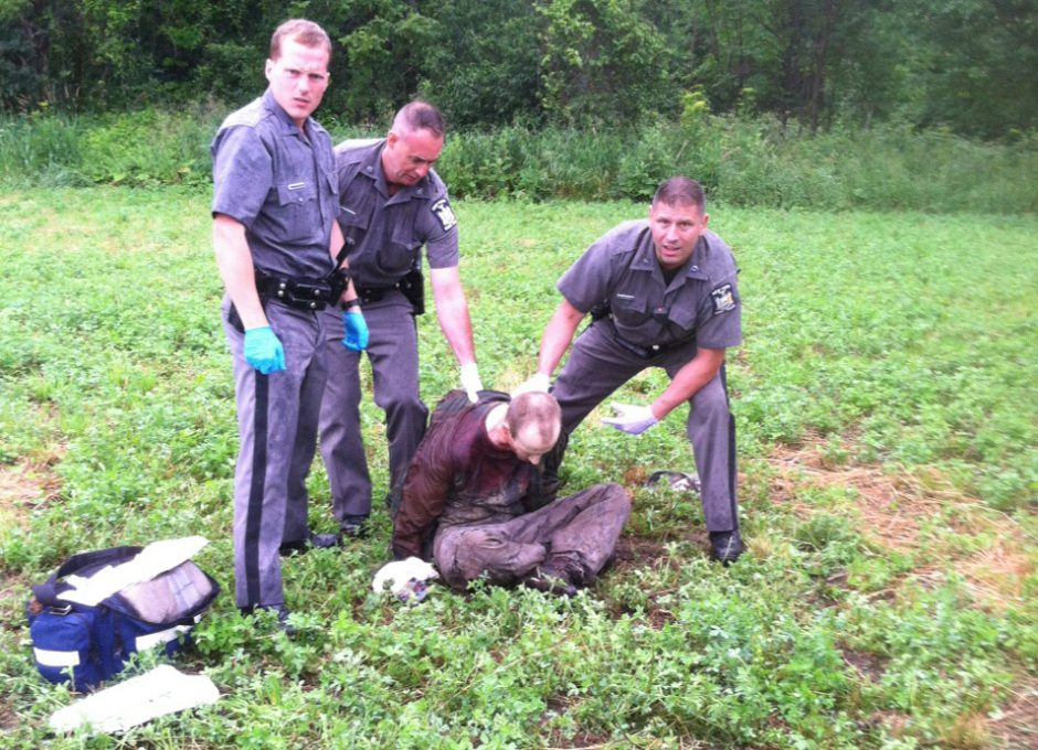 Police stand over David Sweat after he was shot and captured near the Canadian border Sunday, June 28, 2015, in Constable, N.Y.
