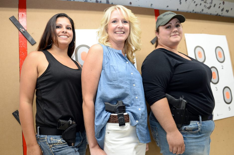 Jodi Vaccaro, left, Kristin Richter, center, and Jessica Braun, members of the local chapter of Well Armed Woman, pose at the Iroquois Rod and Gun Club in Rotterdam.