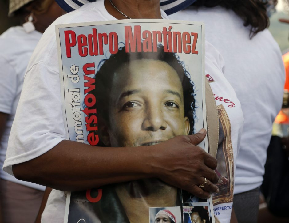 A Pedro Martinez fan carries a poster at the Clark Sports Center before the National Baseball Hall of Fame induction ceremony Sunday in Cooperstown.