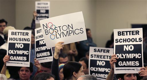 In this Feb. 5, 2015 photo, people hold up placards against the Olympic Games coming to Boston, during the first public forum regarding the city's 2024 Olympic bid, in Boston.