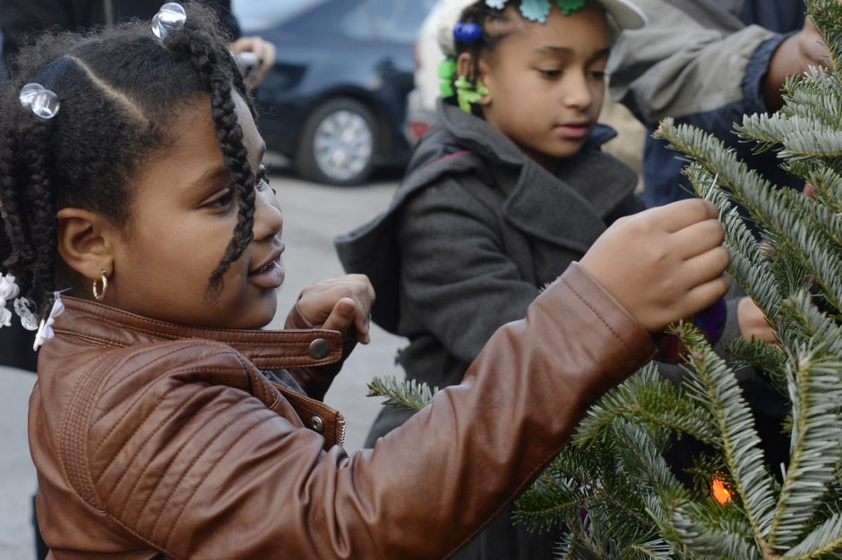 Diamond Brandow, 7, of Schenectady hangs an ornament on the Christmas tree in front of the Hamilton Hill Arts Center on Schenectady Street on Saturday, December 3, 2016.