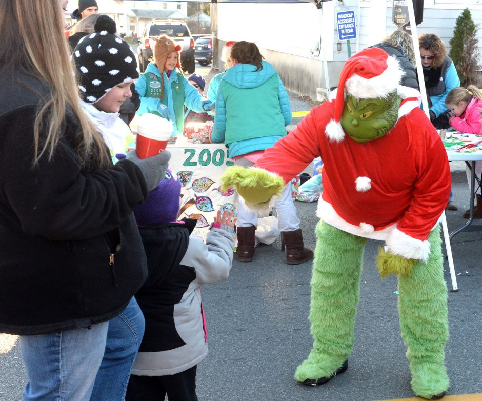 The Grinch gives a high-five to Gauvreau family of Scotia during the Village of Scotia Holiday on the Avenue celebration on Sunday.