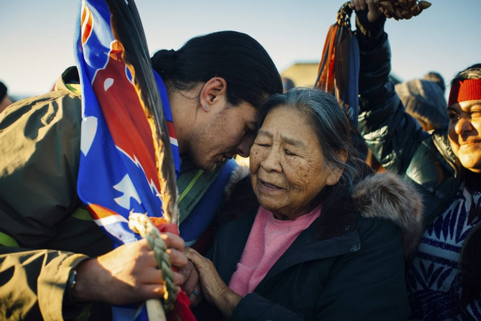 Maida Le Beau, from the Cheyenne River Sioux Tribe, embraces Bobby Robedeaux, of the Echohawk Bayhylle family of the Pawnee Nation in Oklahoma, after learning that permits would not be approved for a section of the Dakota Access Pipeline, at the Oceti ...