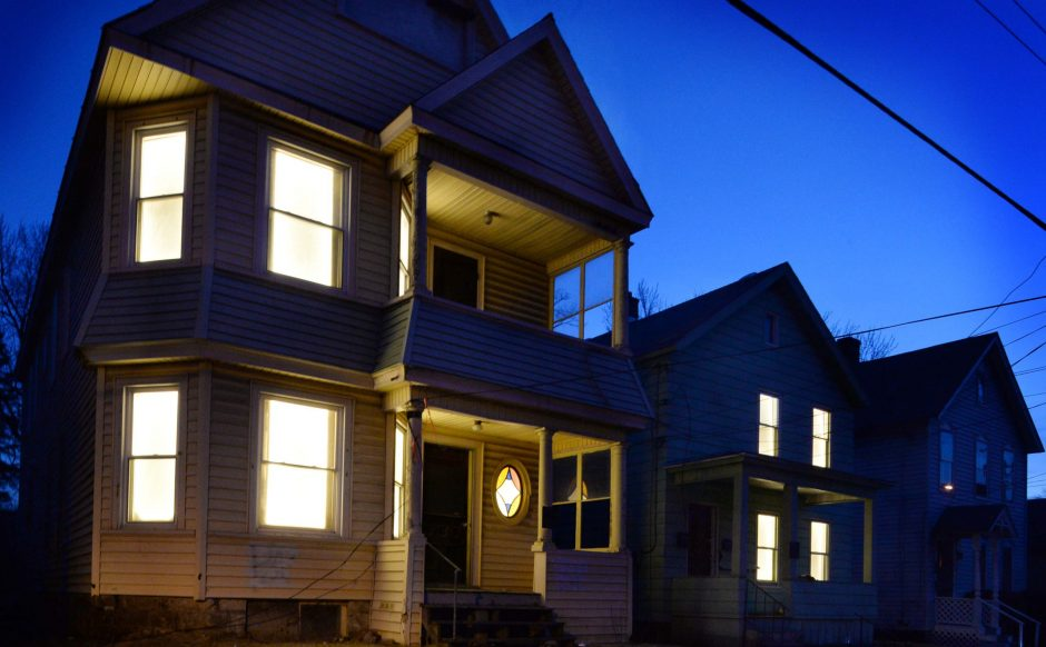 Pulsating lights illuminate the windows of three abandoned properties at 852-854 Eastern Avenue on March 24.