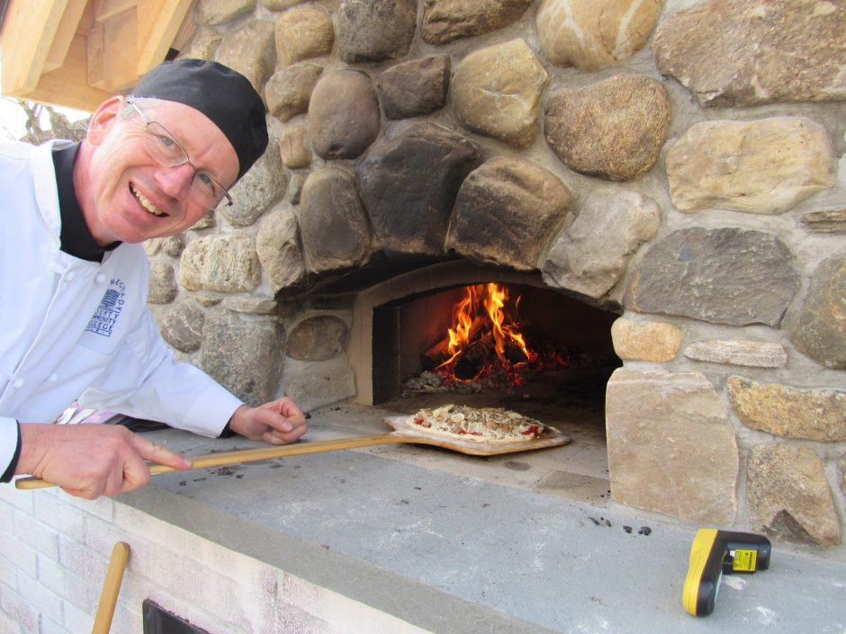 Paul Krebs, a professor in the Schenectady County Community College's school of Hotel, Culinary Arts and Tourism, shows off pizza and flames in the college's new wood-fired brick oven.