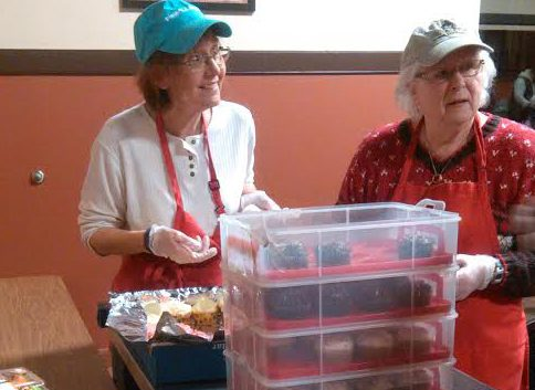 Volunteers from St. John the Evangelist Church hand out cupcakes after a recent community meal at the City Mission.