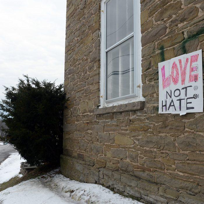 "Swastika graffiti covered by ""Love not Hate"" is seen Jan. 2 on Esperance Presbyterian Church in the village of Esperance"