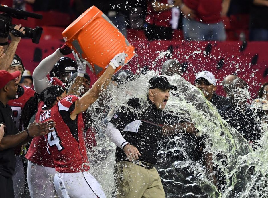 Atlanta coach Dan Quinn is doused with water after the Falcons won the NFC championship Sunday.