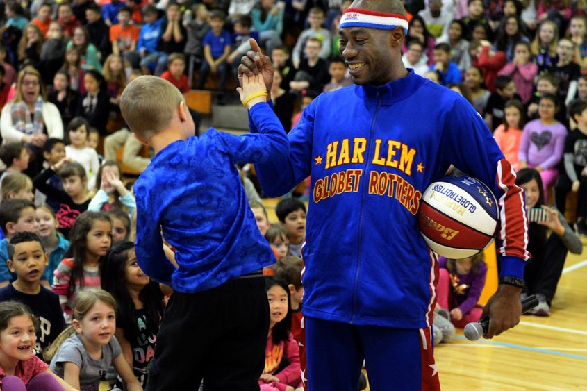 """Harlem Globetrotter Tay """"Firefly"""" Fisher high-fives Calen McKeever at Arongen Elementary School."""