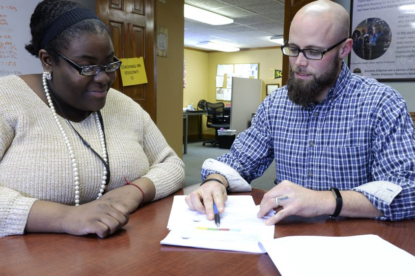 Nathaniel Mandsager, who runs the City Mission's Employer Resource Network, goes over paperwork with Imani Payne.