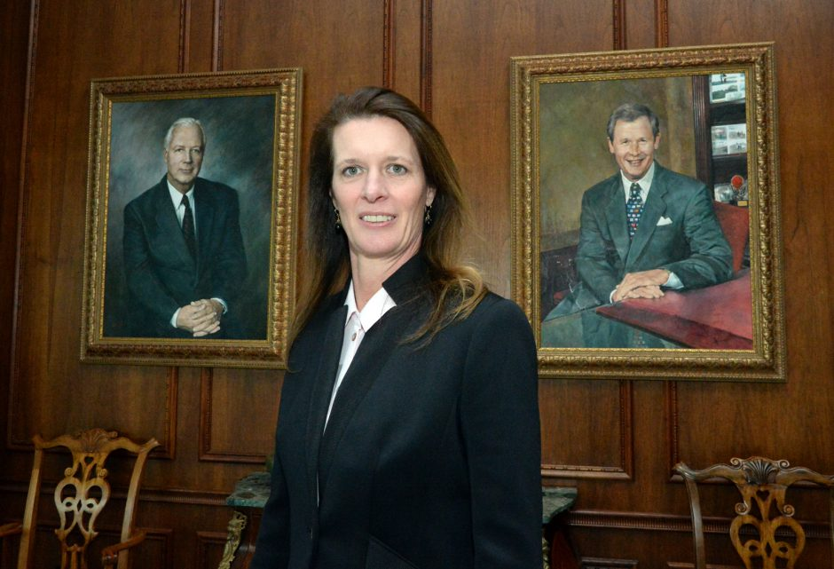 Heather is flanked by paintings of Henry D. Wright, left, and Wallace A. Graham at SI Group.