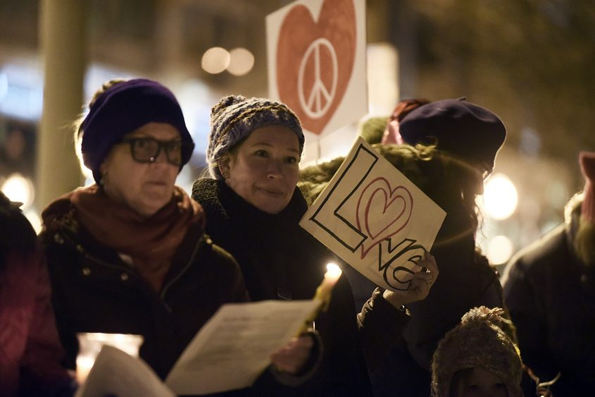 """Heather Sheeley, of Saratoga Springs, holds a """"Love"""" sign at the Valentine's vigil on Tuesday, Feb. 14, 2017."""
