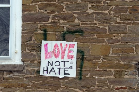 A swastika painted on the Esperance Presbyterian Church in January is covered by a sign promoting love over hate.