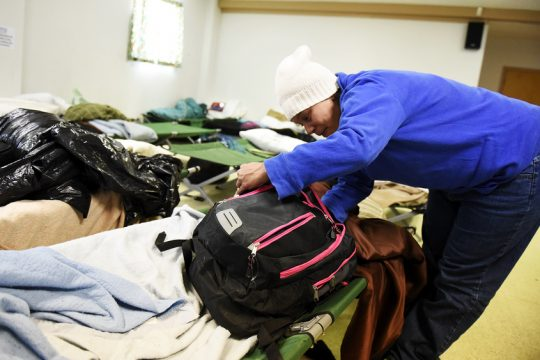 Dayna Gussman goes through her belongings in the Saratoga Springs Cold Blue Shelter last week.