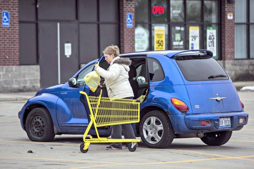 A woman unloads a shopping cart outside a Dollar General Corp. store in Warren, Michigan.