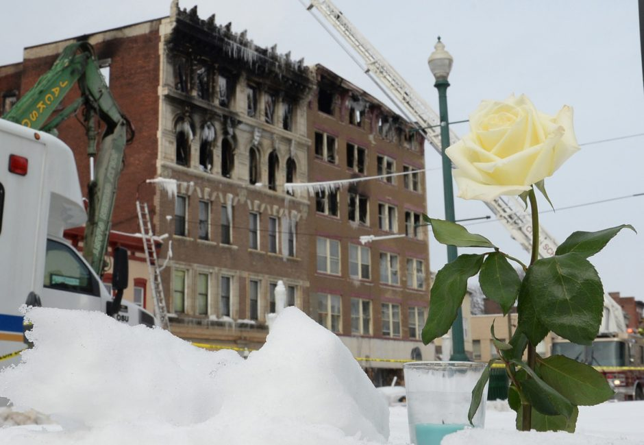 A friend of a victim placed this candle and flower in the snow in front of the buildings on Jay Street destroyed by fire.