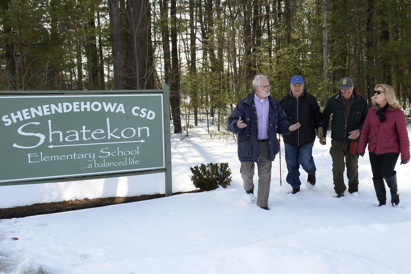Bob Rybak, left, Frank Berlin, Jim Ruhl and Susan Burton walk Tuesday near land considered for sale by the school district.