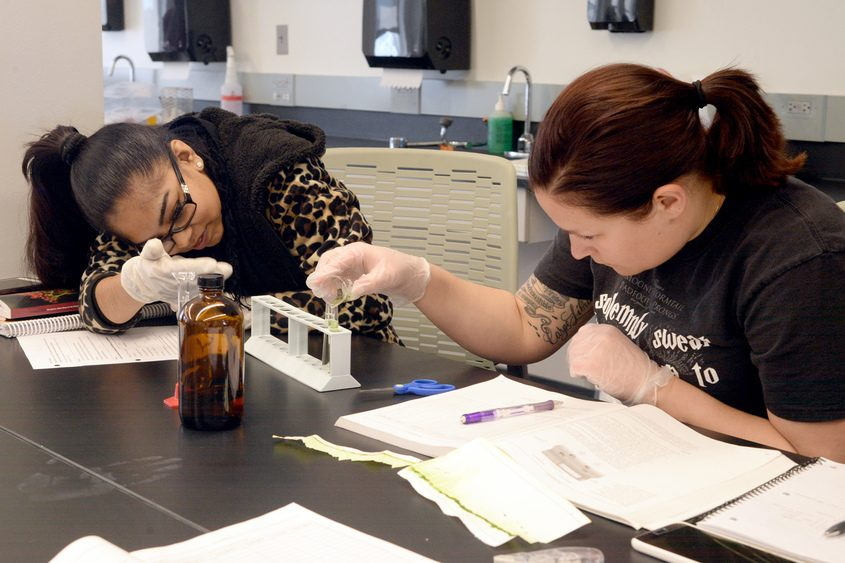 Students Surita Ramsarat (left) and Kayla Luding prepare vials of acetone and spinach dye to input into a spectrophotometer.