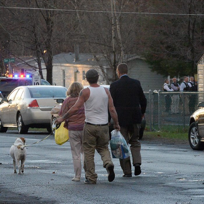 State police Capt. Robert Patneaude (right) escorts a family to their home Sunday, near a standoff on Fern Lane in Halfmoon.